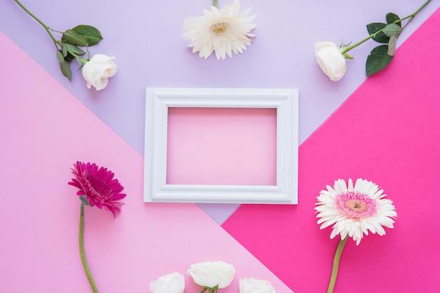 Marco en blanco con diferentes flores en la mesa