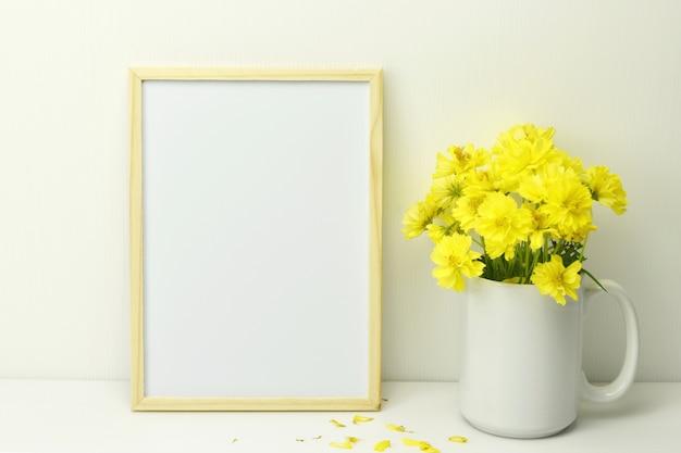 Marco en blanco con flores amarillas en florero