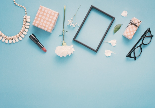 Marco en blanco con flores, cajas de regalo y lápiz labial en la mesa