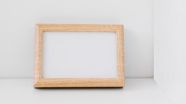 Marco en blanco de madera apoyado contra pared