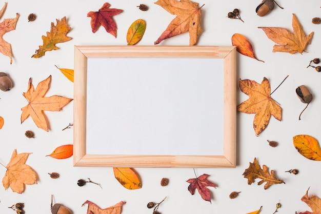Marco blanco de madera sobre fondo de hojas de otoño