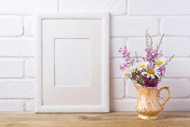 Marco blanco con manzanilla y flores de color púrpura en jarra dorada
