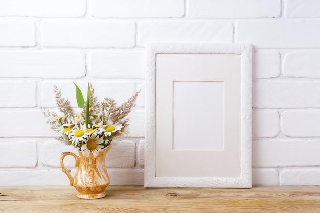 Marco blanco con manzanilla y hierba en florero dorado