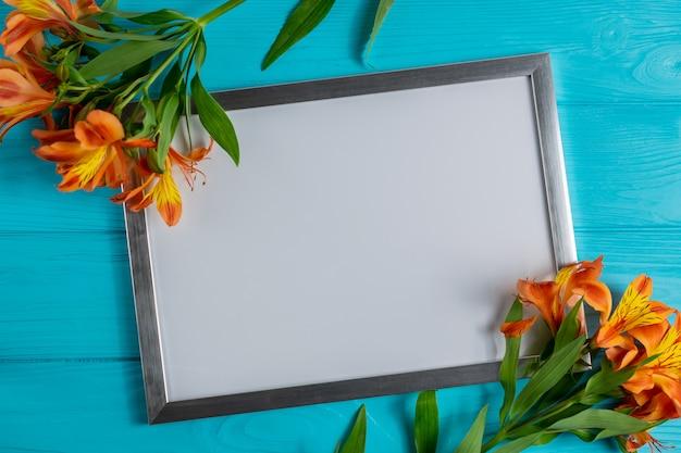 Marco blanco maqueta con copia espacio para texto en madera azul con flores de alstroemeria