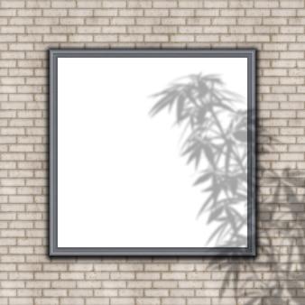 Marco en blanco en la pared de ladrillo con superposición de sombra de planta