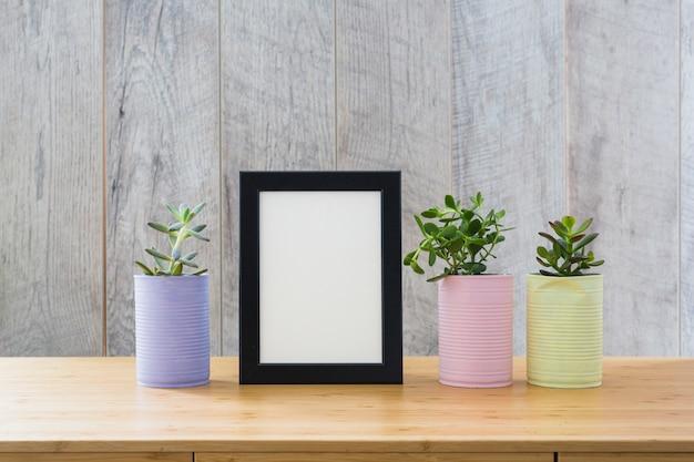 Marco blanco con plantas de cactus en lata pintada en escritorio de madera