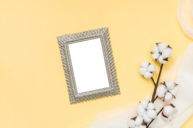 Marco en blanco con rama de algodón en mesa amarilla