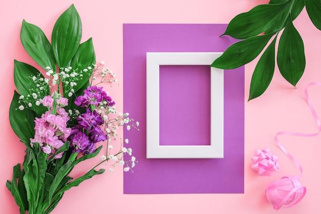 Marco blanco y ramo de flores en la pared de color rosa púrpura.