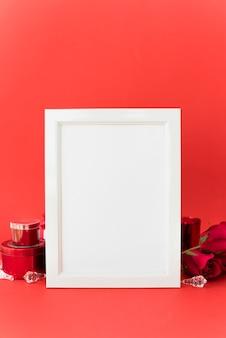 Marco en blanco con rosas en la mesa