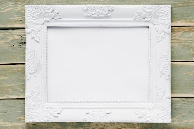 Marco blanco sobre fondo de madera