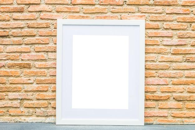 Marco en blanco sobre fondo de pared de ladrillo