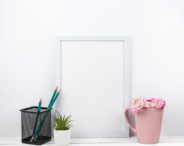Marco blanco vacío; estante para lápices flores y plantas suculentas en mesa.