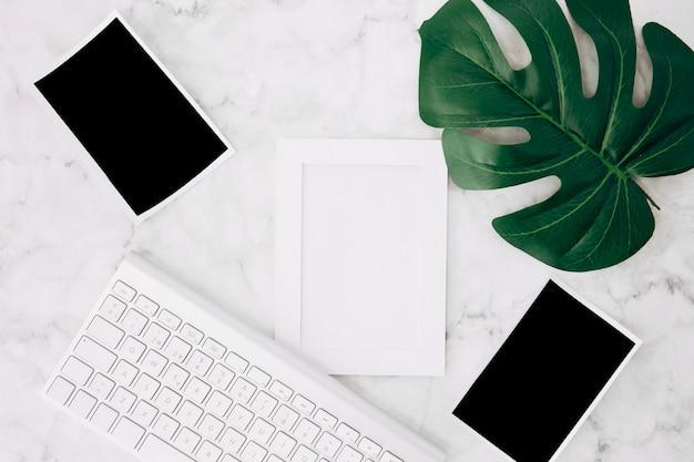 Un marco blanco vacío y fotos polaroid con hoja de monstera verde y teclado en el escritorio