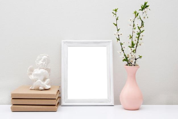 Marco blanco vacío maqueta con jarrón rosa y libros sobre la mesa. marco de madera para su texto.