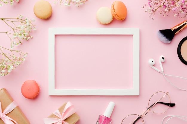 Marco blanco vacío rodeado de accesorios de maquillaje