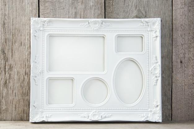 Marco blanco vacío sobre fondo de madera.