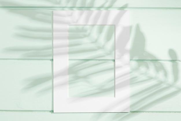 Marco blanco vertical con sombra de hoja