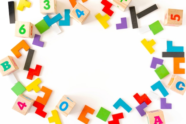 Marco de bloques de madera de diferentes formas coloridas sobre fondo blanco. juguetes naturales y ecológicos para niños. concepto de pensamiento creativo y lógico. endecha plana. copt space.