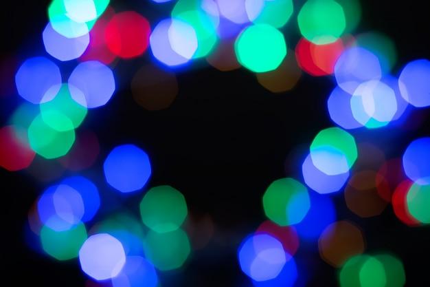 Marco bokeh brillante multicolor sobre fondo negro. resumen brillo negro, verde, morado, rojo y azul