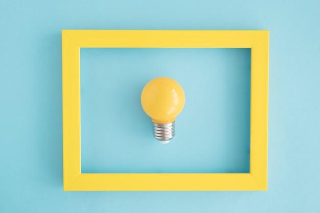 Marco de bombilla de luz amarilla sobre fondo azul