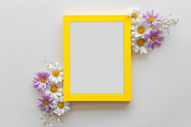Marco de borde amarillo decorado con hermosas flores contra la superficie blanca