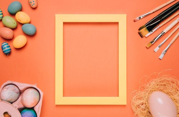 Marco de borde amarillo rodeado de huevos de pascua; nido y pinceles sobre un fondo naranja.