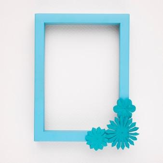 Un marco de borde azul vacío con flores sobre fondo blanco.