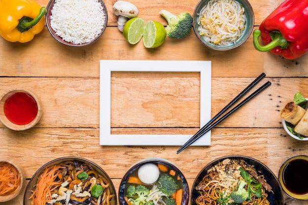 Marco de borde blanco con palillos y comida tradicional tailandesa en escritorio de madera