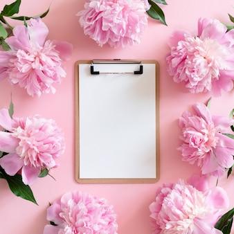 Marco de borde hecho de peonías. maqueta del tablero de clip en un fondo de color rosa pastel
