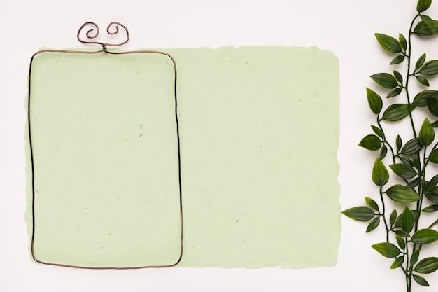 Marco de borde metálico sobre papel verde menta cerca de las hojas sobre fondo blanco.