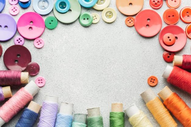 Marco de botones de colores y rollos de hilo con espacio de copia