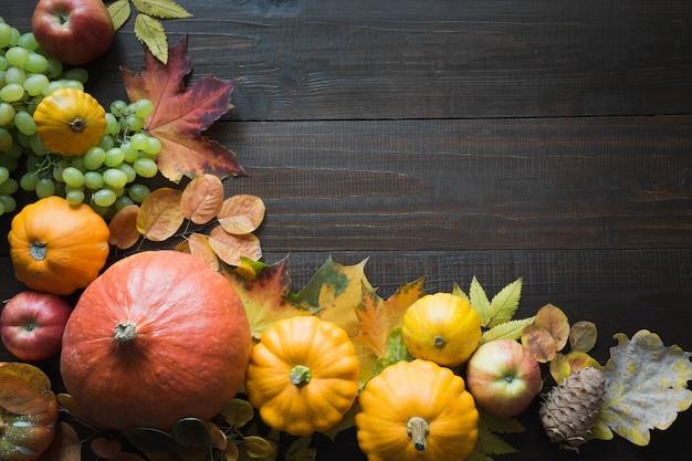 Marco de calabaza y hojas de arce sobre tabla de madera con patrón de otoño vista superior