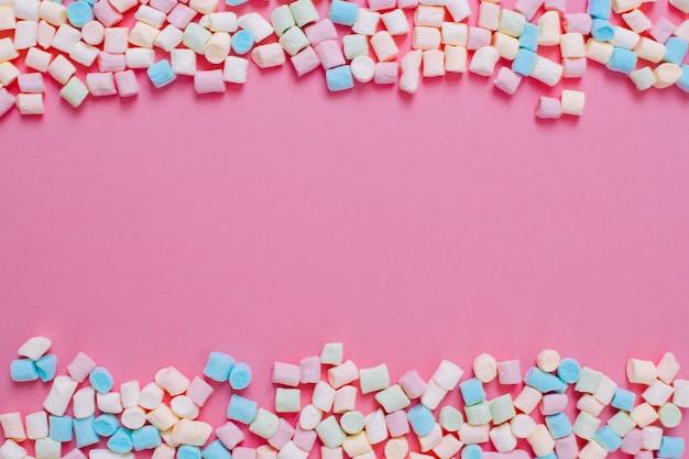 Marco de caramelos de malvavisco dulce blanco y rosa con espacio de copia sobre un fondo rosa.