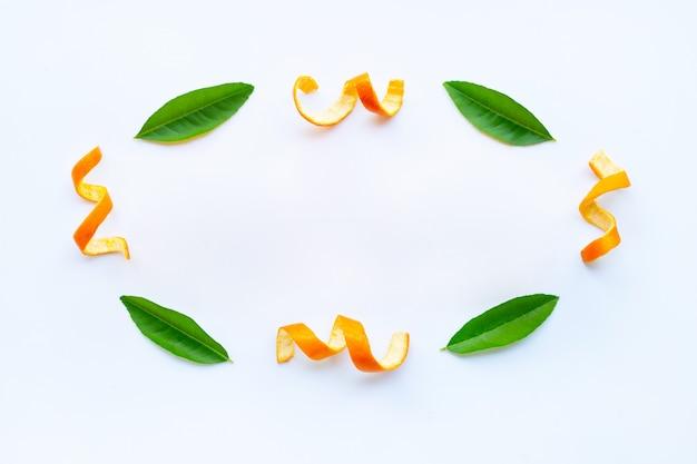 Marco de cáscaras de naranja con hojas verdes sobre blanco