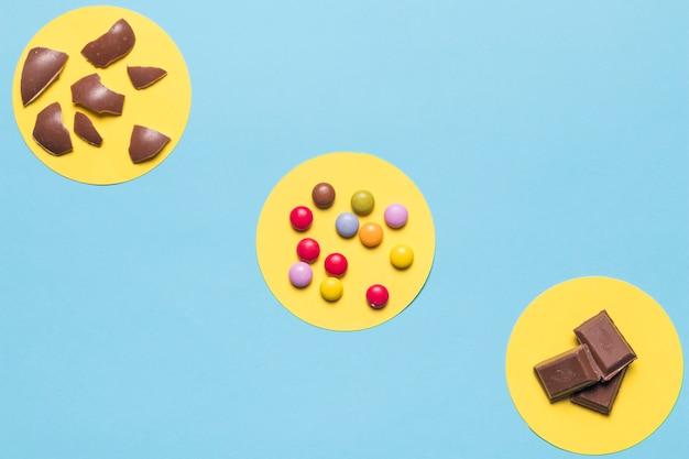 Marco circular amarillo sobre los caramelos de gemas de colores; cáscaras de huevo de pascua y trozos de chocolate sobre fondo azul