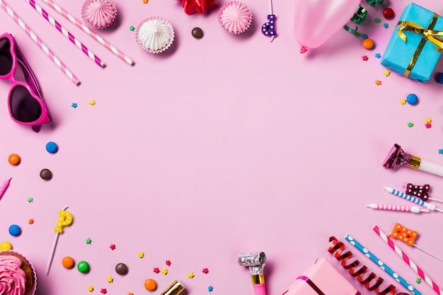 Marco circular en blanco hecho con artículos de fiesta de cumpleaños sobre fondo rosa