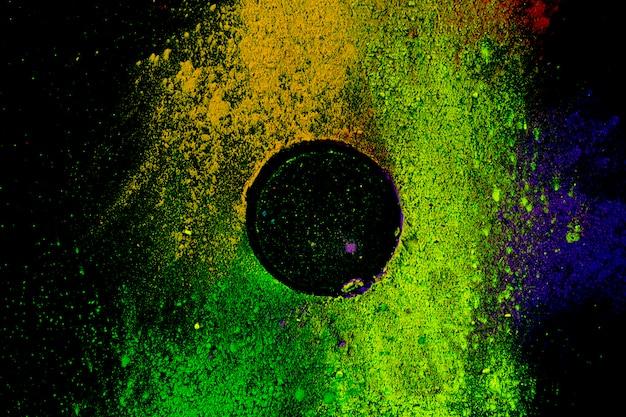 Marco circular de color en polvo tradicional multicolor sobre fondo negro