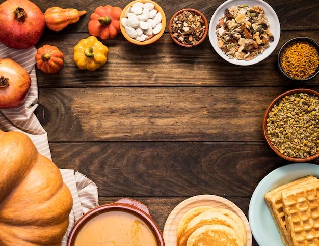 Marco circular de comida en hoja de rayas y fondo de madera.