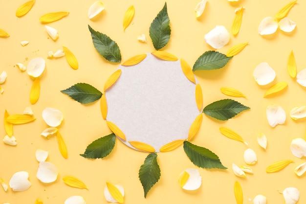 Marco circular decorado con hojas y pétalos sobre fondo amarillo.