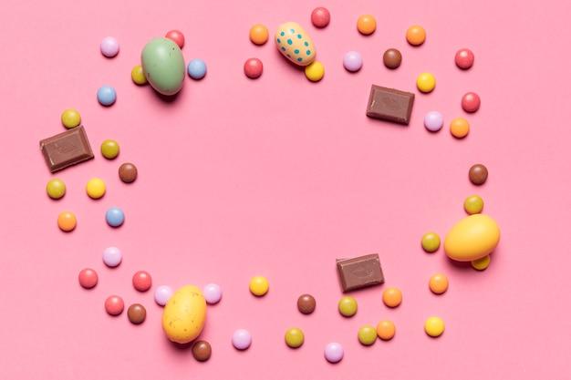 Marco circular hecho con huevos de pascua enteros y caramelos de gemas multicolores sobre fondo rosa
