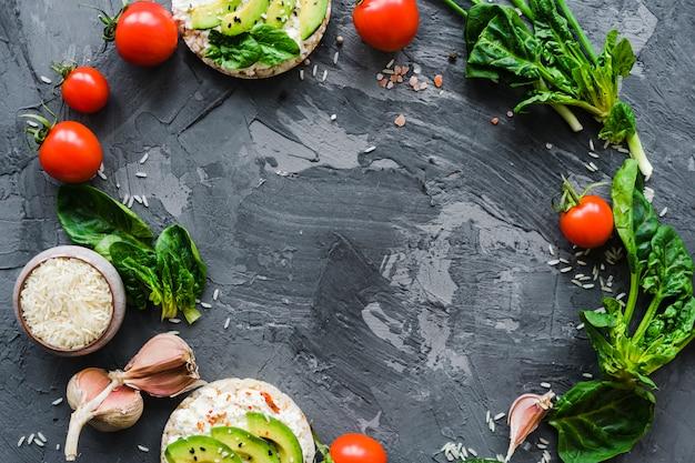 Marco circular hecho con verduras frescas y bocadillos saludables sobre papel tapiz de cemento desgastado