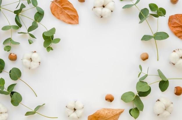 Marco circular plano con hojas y flores de algodón.