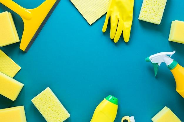 Marco circular plano con productos de limpieza amarillos.