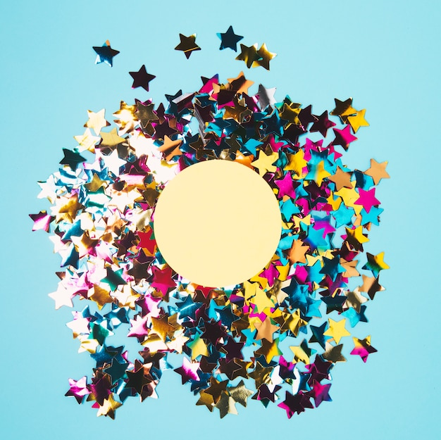 Marco circular sobre el confeti de forma de estrella de colores sobre fondo azul