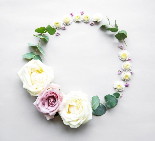 Marco de círculo decorativo con rosas y hojas rosas y blancas, corona sobre fondo blanco. lay flat