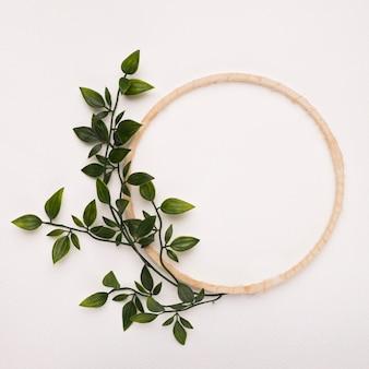 Marco de círculo de madera con hojas artificiales verdes sobre fondo blanco.