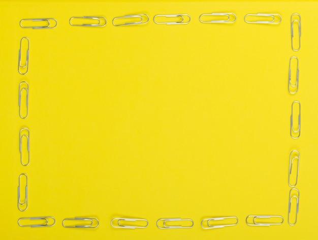Marco de clips de papel de nota sobre fondo amarillo