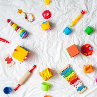 Marco colorido brillante de los juguetes de los niños en el fondo blanco. vista superior. lay flat. copia espacio para te