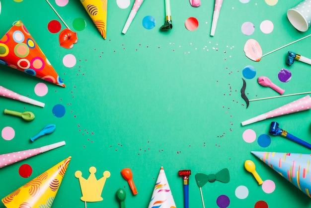 Marco colorido del cumpleaños con los artículos multicolores del partido en fondo verde