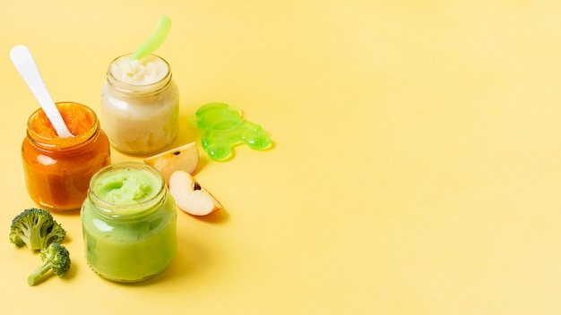 Marco de comida para bebés en frascos sobre fondo amarillo